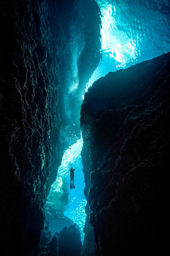 Island with natural beauty Adventure Aquatic Sport Beauty In Nature Cave Group Of People Ice Leisure Activity Lifestyles Nature Outdoors People Real People Rock Rock - Object Scuba Diving Sea Sport Swimming UnderSea Underwater Unrecognizable Person Water