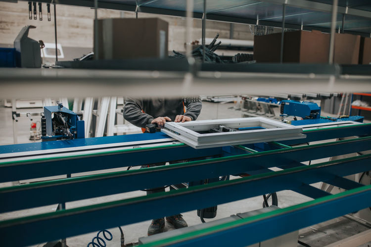 Low section of manual worker making window frame at factory