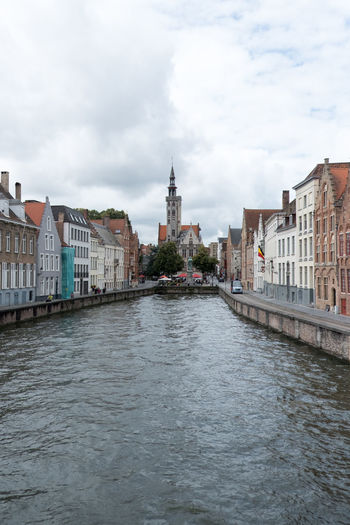 Canal lined with houses in Bruges, Belgium with Pootersloge in the distance. Water canal with old houses in Belgium, Europe. Bruge Bruges Canal BrugesCanal Poortersloge Brugge Bruge Street Bruges