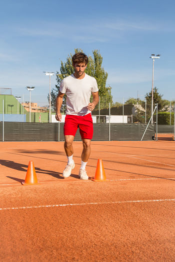 Full Length Of Young Man Exercising At Tennis Court