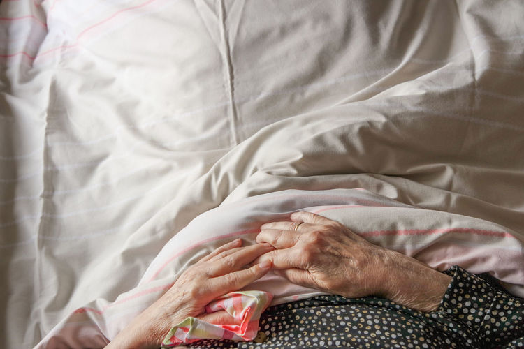 Caring for an aging parent Hospital Nurturing Bed Caring Close-up Compassion Day Elderly Elderly Woman Grandmother Human Body Part Human Hand Illness Indoors  Lying Down Medical Need Old Woman Patience Patient Senior Senior Women Sheet Wrinkled Skin