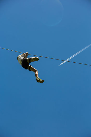 Low Angle View Of Teenage Boy Zip Lining Against Clear Blue Sky During Sunny Day