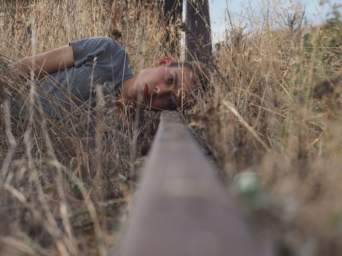 Portrait Of Young Man Lying On Railroad Track