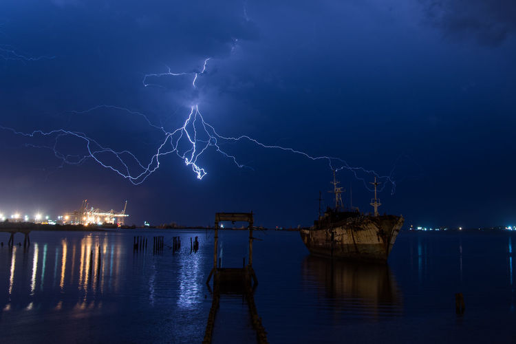 Lightning Cityscape City Water Illuminated Forked Lightning Thunderstorm Power In Nature Urban Skyline Business Finance And Industry Storm Cloud Horizon Over Water Storm Ocean Dramatic Sky Sky Only Electricity Pylon Electricity Tower Calm Extreme Weather