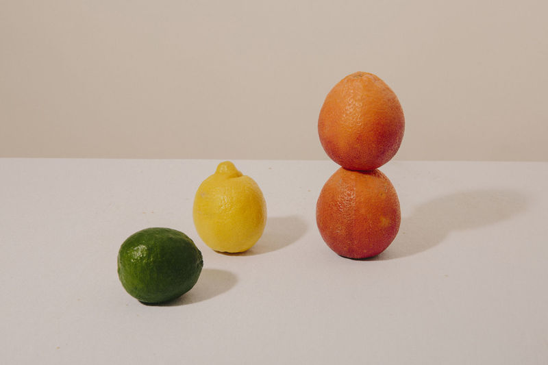 Close-up of oranges on table against white background