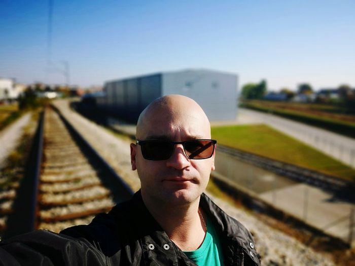 Portrait of man wearing sunglasses at railroad station