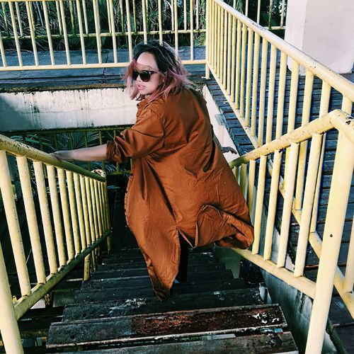 High Angle View Of Woman Wearing Brown Coat On Staircase
