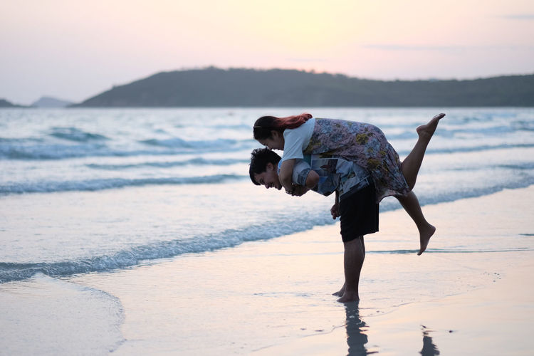Side View Of Man Piggybacking Woman At Beach Against Sky During Sunset