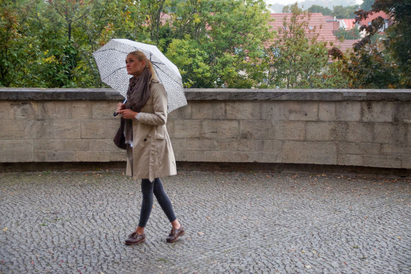 Full Length Of Woman With Umbrella Walking On Footpath