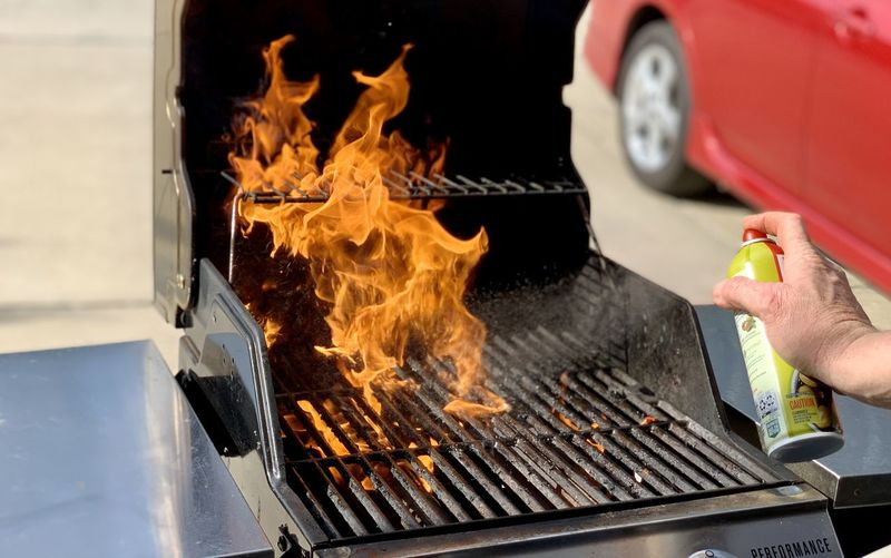 Midsection of person with fire on barbecue grill