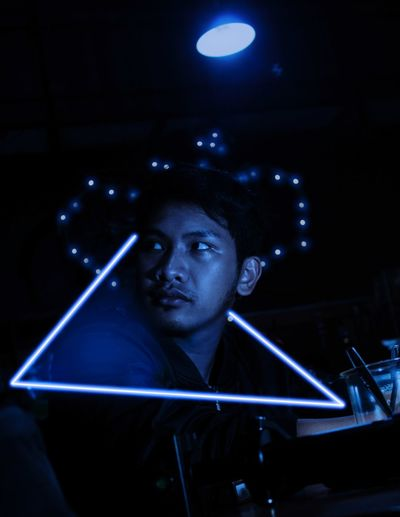 Close-up of young man looking away through illuminated triangle