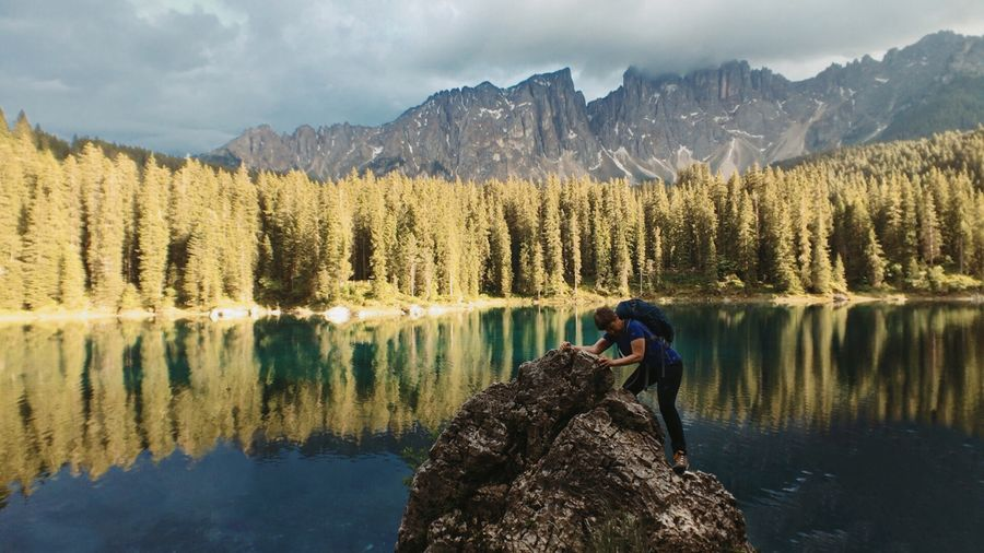 Man standing on rock by lake against mountains