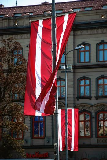 Latvian flags hanging on poles Patriotic Patriotism Flags Riga Latvia Building Exterior Flag Architecture Built Structure Patriotism Day Window Hanging Red No People Pride National Icon Striped Outdoors Sunlight Building
