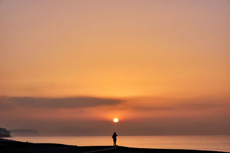 Silhouette people standing by sea against sky during sunrise