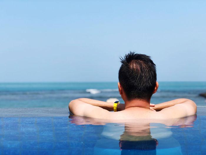 Rear view of man in infinity pool against sky