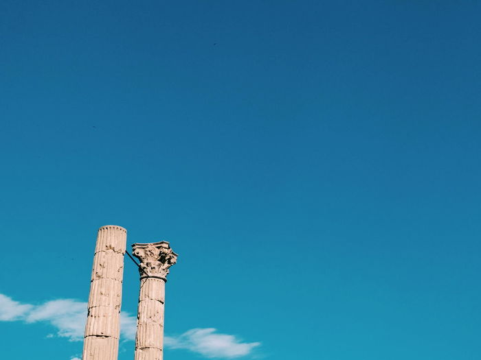 Low angle view of roman columns against blue sky