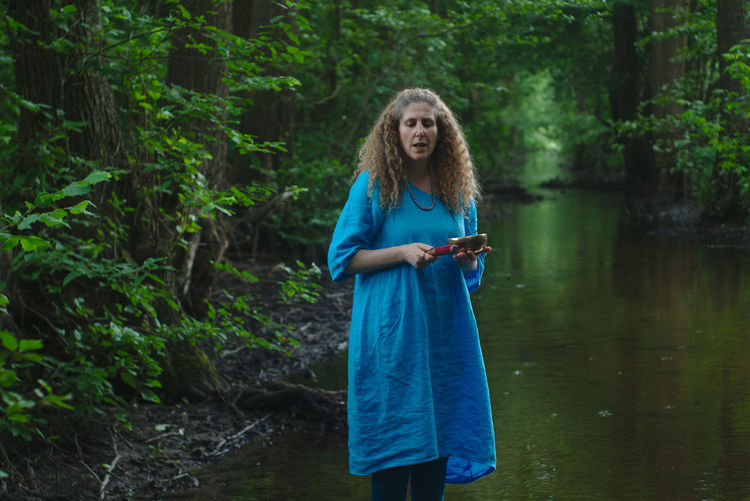 Full length of woman standing on water in forest