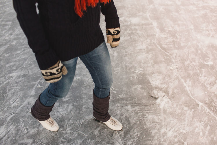 Close up of a woman learning to ice skate December Frozen Ice Natural Pond Winter Woman Cold Female Gloves Hobby Ice Skater Ice Skating Knitwear Lake Leisure Activity Outdoor Rink Season  Skates Skating Snow Snowy Sport Sunset
