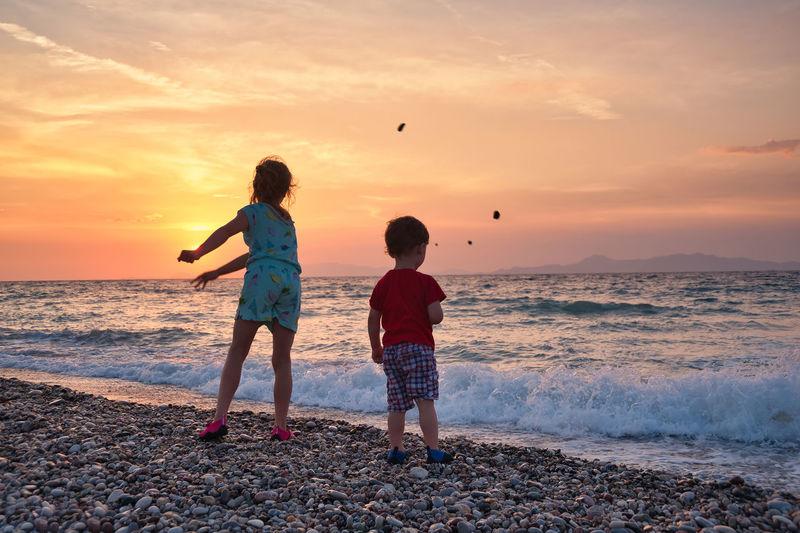 Summer memories. children throwing pebbles to sea during sunset.