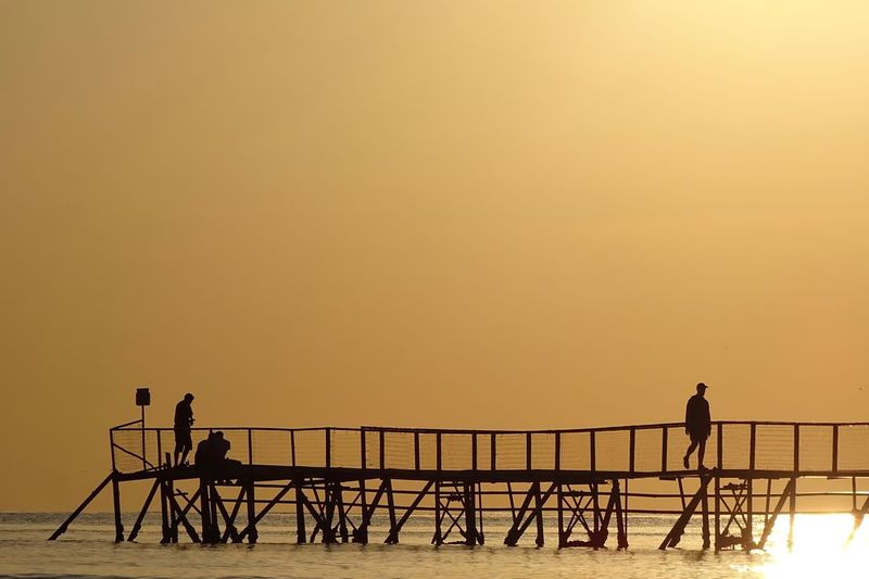 Silhouette People On Pier Over Sea During Sunset