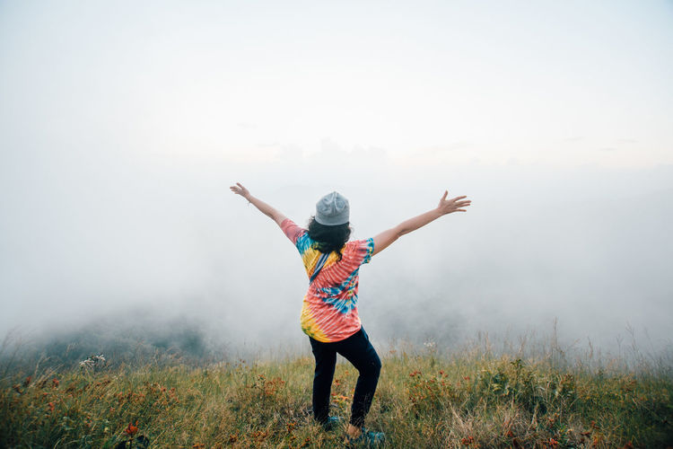 Rear view of woman with arms outstretched standing on mountain during foggy weather