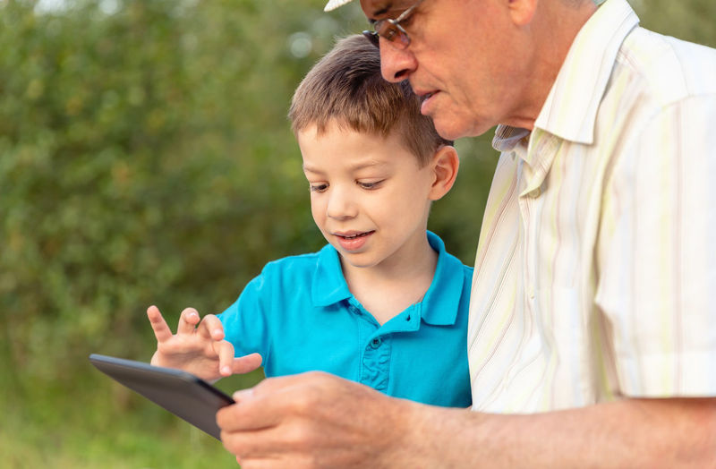 Closeup of grandchild teaching to his grandfather to use a electronic tablet over nature background. Generation values concept. Caucasian Age Hat Parent Real Communication TAB Touchscreen Complicity Reading Together Education Internet Sitting Male Adult Background Man Kid Child People Happy Boy Touchpad Technology Pad Leisure Lifestyle Old Two Elderly Outdoors Bench Closeup Park Nature Family Generation Using Learning Learn Teaching Teach Electronic Tablet Senior Grandparent Grandfather Grandchild Grandson