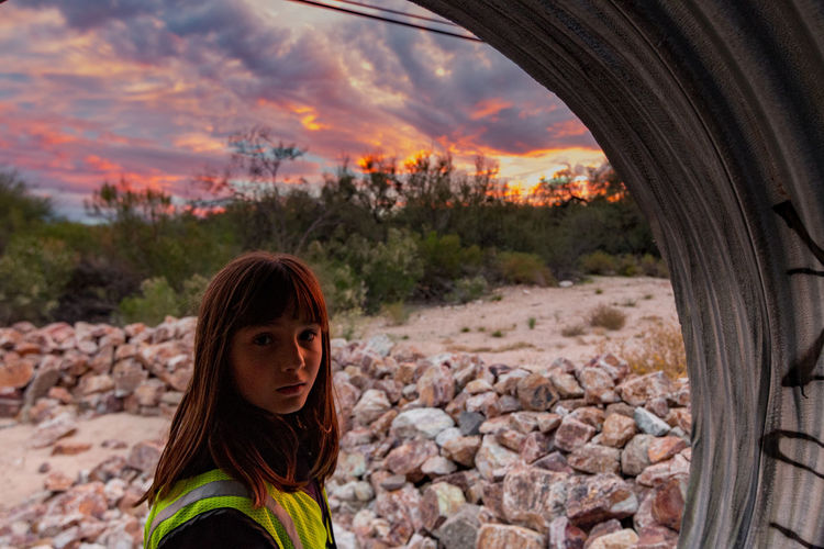 Portrait of girl in tunnel during sunset