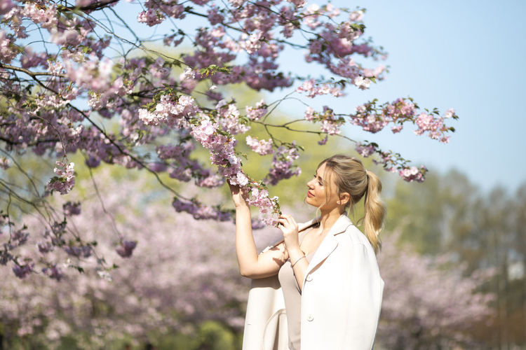Low angle view of woman standing by flowering tree