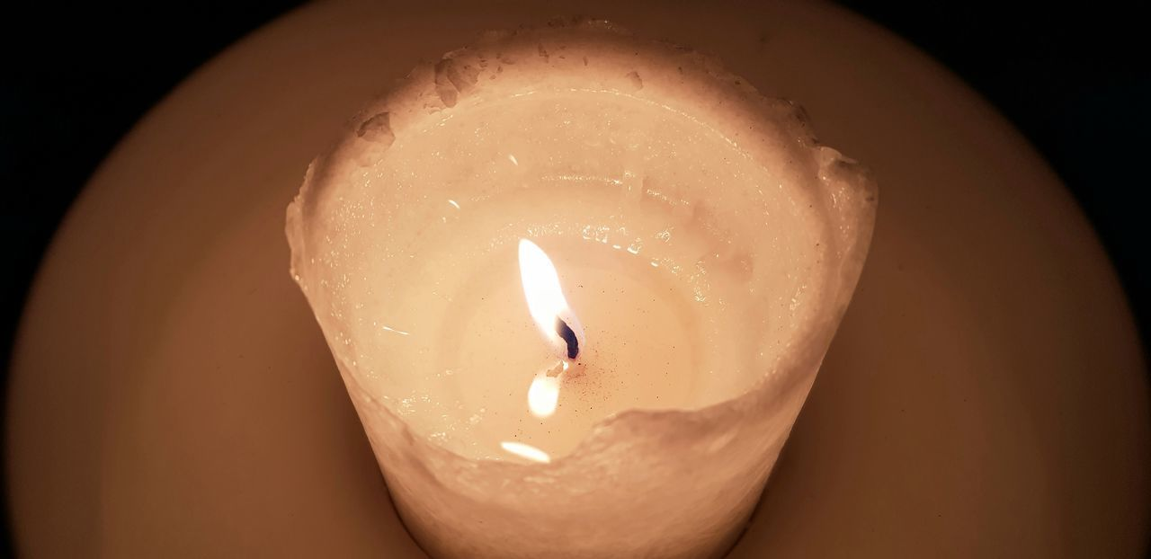 HIGH ANGLE VIEW OF LIT CANDLE IN DARK