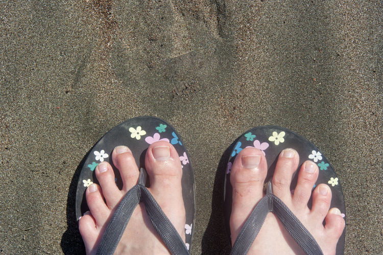 Low section of person wearing flip-flop at beach