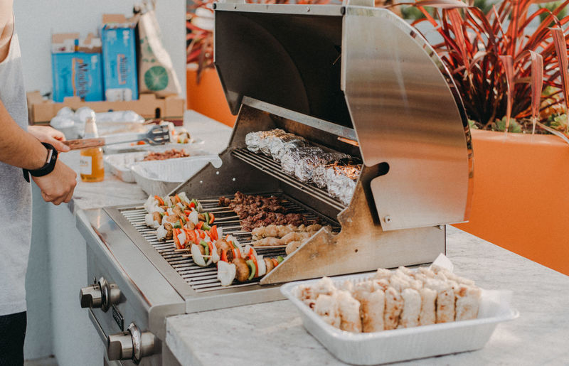 Midsection of man preparing food on barbeque grill at table