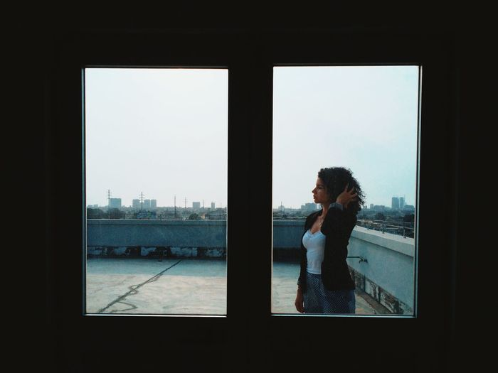 Womman Standing By Window On Rooftop