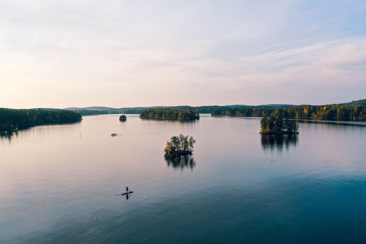 Aerial view of lakes, islands, forest and a person paddle boarding