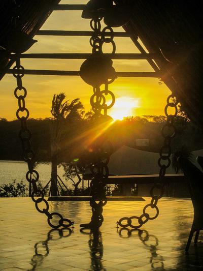 Menjangan Sundown Bali Menjangan Architecture Built Structure Chain Hang Hanging Illuminated Lighting Equipment Metal Nature No People Silhouette Sky Sun Sundown Sunlight Sunrise Sunset Water #urbanana: The Urban Playground