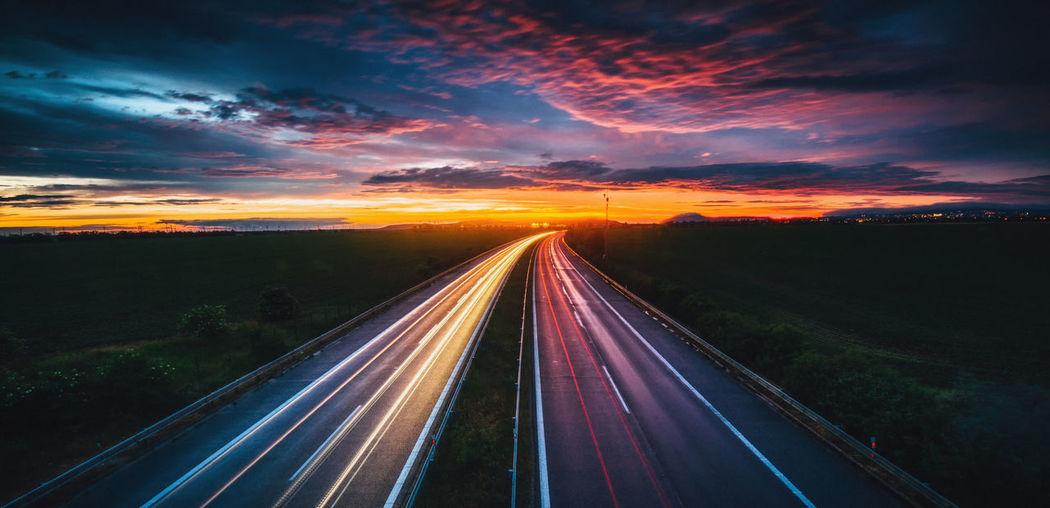 Light trails on highway against sky during sunset