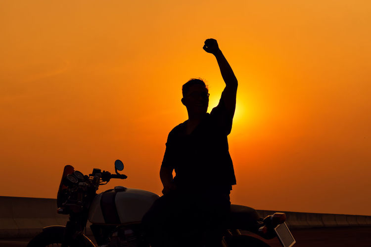 Motorcycle on the way back on a summer trip, silhouette man riding a motorcycle, freedom concept.