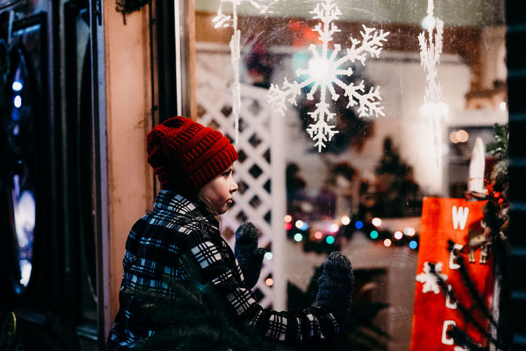 Christmas Celebration Winter Real People Hat Lifestyles Clothing Knit Hat Warm Clothing Holiday Leisure Activity Decoration Christmas Decoration One Person christmas tree Waist Up Illuminated Event Looking Christmas Ornament Outdoors Christmas Lights Childhood Girl