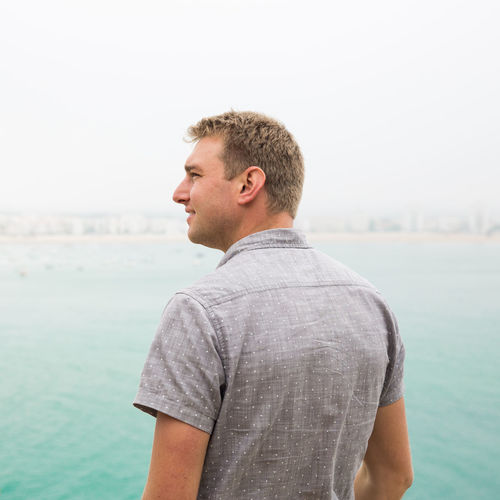 Rear view of man looking away while standing by sea against sky