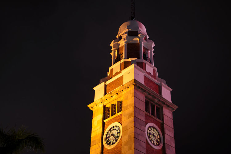 Low angle view of clock tower against clear sky at night