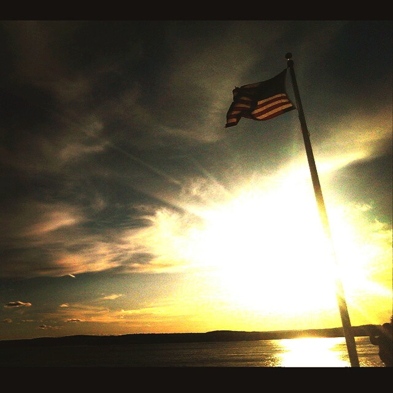 flag, patriotism, flag pole, sunset, sky, wind, sea, pride, no people, low angle view, cloud - sky, outdoors, stars and stripes, nature, water, horizon over water, beauty in nature, day