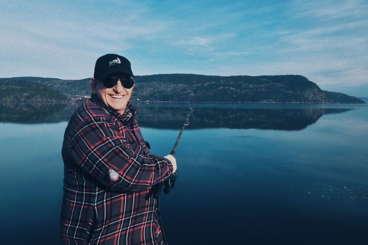 Portrait of happy man fishing at lake against sky