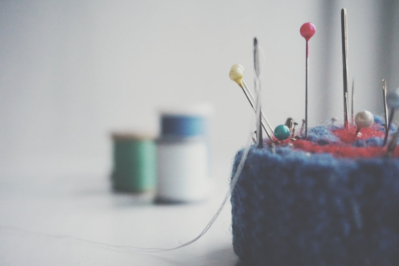 indoors, sewing, selective focus, no people, wool, spool, sewing item, close-up, needle, multi colored, knitting needle, day