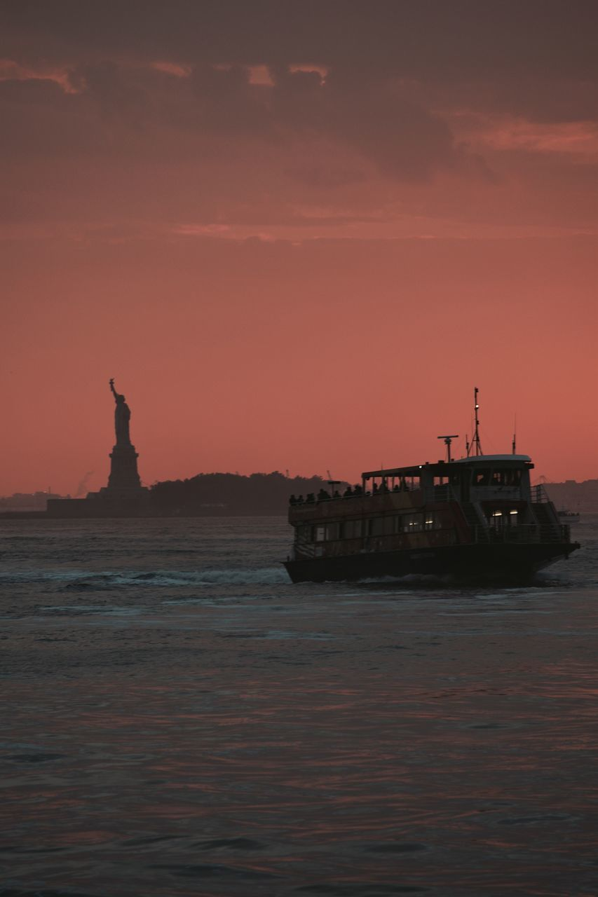 Silhouette Boat And Statue Of Liberty In Sea During Sunset At Liberty Island
