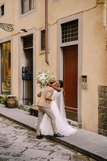 Couple embracing while standing against building in alley