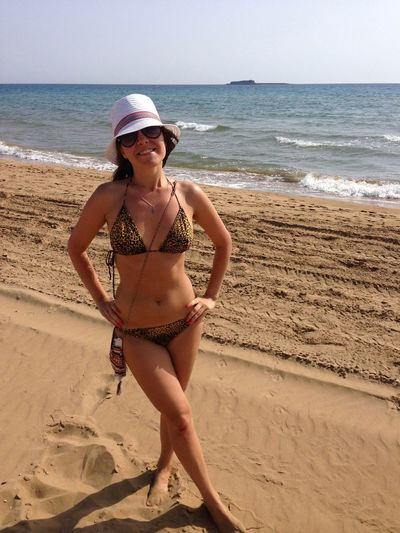 Portrait of sensuous woman in bikini standing at beach