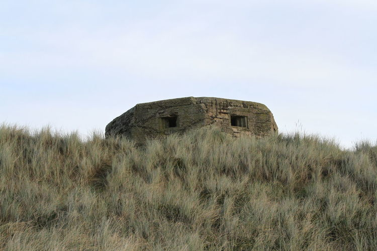 Low angle view of abandoned pill box on grassy field