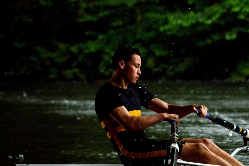 Athlete rowing on river