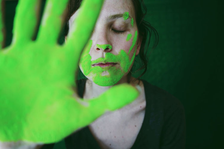 Close-up of woman gesturing with green hand