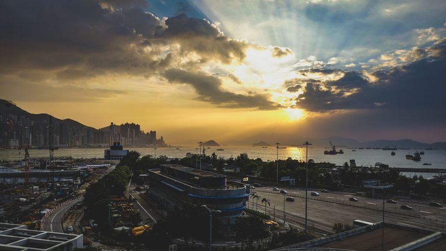 Panoramic view of coastal city against cloudy sky during sunset