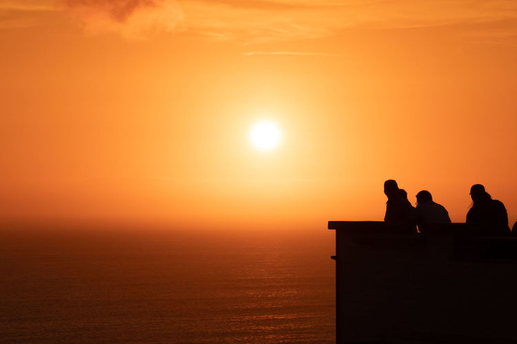 Sky Silhouette Sunset Water Sun Beauty In Nature Men Group Of People Orange Color Sea Nature Togetherness Leisure Activity Scenics - Nature Women Real People People Sitting Copy Space Horizon Over Water Outdoors Looking At View